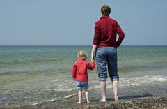 Young woman and her little doughter are standing at the beach and looking ove Stock Photos