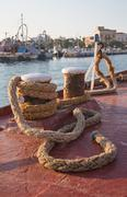 old sisal rope of an ancient ship fixed on the docks in the harbor. - stock photo