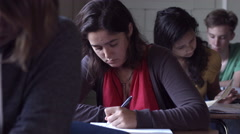 CU Girl writing an assignment in classroom 4K - stock footage