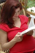Pregnant woman reads a book Stock Photos