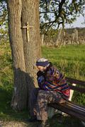 Man sitting on bench beyond tree with cross at Grossau near Bad Voslau Lower Stock Photos