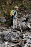 Eight year old boy on rock in desiccated creek, alpes, austria Stock Photos