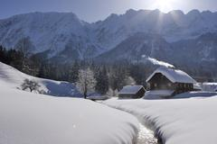 a old wooden house on a creek and a lot of snow in the background the mountai - stock photo