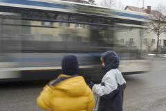 two boys waiting at the streetside while a bus passes by - stock photo