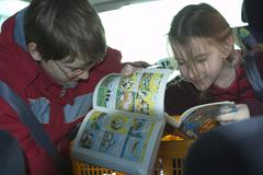 Children in the car reading comic strips Kuvituskuvat