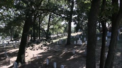 Slow pan of a cemetery during the day with sunshine and trees Stock Footage