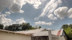 Time lapse of clouds in HDR with shed and fence in shot - stock footage
