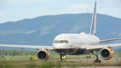 Airplane taxiing at Oslo Airport turning right another plane takeoff in distance Stock Footage