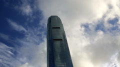 Hong Kong IFC building with  fast moving clouds over blue sky time lapse         Stock Footage