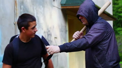 Teenager with a backpack against aggressive man with a baseball bat - stock footage