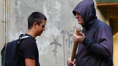Teenager with a backpack against aggressive man at outdoor - stock footage