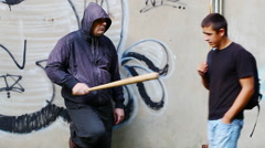 Aggressive man with a baseball bat talking with teenager - stock footage