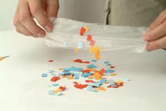 Stock Photo of Statische aufladung papierschnipsel kleben an folie tute fest static charge
