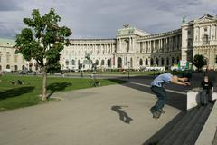 A skatboarder and the building of the hofburg viewed from the public garden v Stock Photos