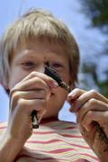 nine-year-old boy with dirty face fabricating arrowhead - stock photo