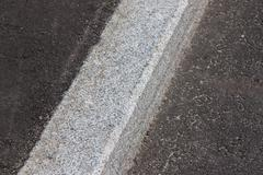 white curb and asphalt road - stock photo