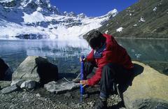 Woman filtrating drinking water at gokyo lake nepal Kuvituskuvat