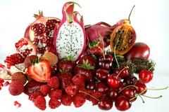 assorted red fruit on white background - stock photo