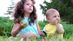 Stock Video Footage of Cute girl and her little brother having fun with soap bubbles on grass