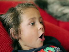 Boy lying on red sofa and singing a song Stock Footage
