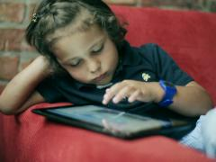 Bored child playing on tablet and sitting on red sofa Stock Footage