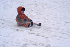 Fife year old boy sliding down a slope Kuvituskuvat