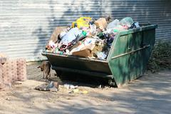 Overfilled trash dumpster in ghetto neigborhood in Russia - stock photo