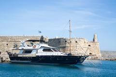 Greek island crete in the cyclades: sightseeing on the old port with fort and Stock Photos