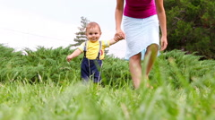 Cute baby boy making his first steps on grass - stock footage