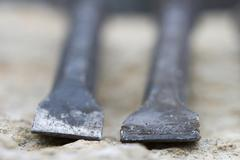 Stock Photo of detail from the sharp edge of two used black chisel.
