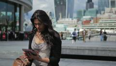 Woman Reading on a Tablet, City of London Backdrop, Mid Shot Stock Footage
