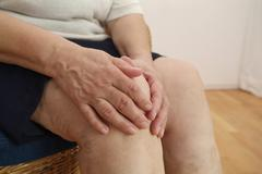 woman with arthrosis seizes herself to kneels - stock photo