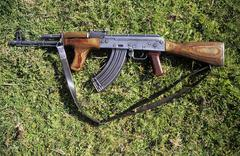 kalashnikov or ak 47 lying on a meadow - stock photo
