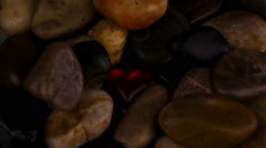 Red crystal heart pulsating among stones - stock footage