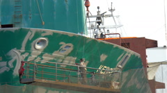 A ship worker repainting some green parts of the big ship, gh4 Stock Footage