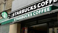 Starbucks Coffee shop (exterior) - people walking on pavement Stock Footage