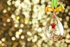 christmas magic light background with glass bauble and colorful ribbon - stock photo