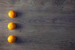 three oranges are on empty dark wooden table - stock photo