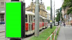 billboard - green screen - urban street with passing cars and trams and building - stock footage