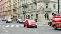 Urban street with passing cars and pedestrian crossing: people walking Stock Footage