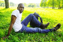 Young african american man in white shirt  with rucksack in a park Stock Photos