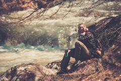 young hiker woman sitting on near fast river with bottle in her hand - stock photo