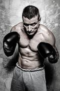 young sporty man in boxing gloves posing - stock photo