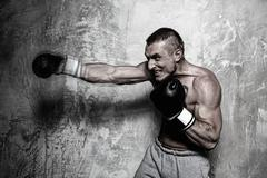 young man in boxing gloves making punch - stock photo