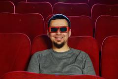 Funny  man in 3d glasses watching movie in cinema Kuvituskuvat