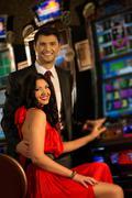 Beautiful young couple near slot machine in a casino Stock Photos