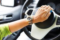 woman hand pressing on a car horn - stock photo