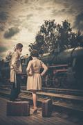 Beautiful vintage style couple with suitcases on  train station platform Stock Photos