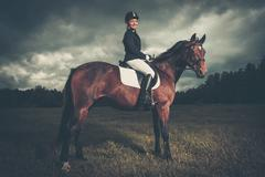Stock Photo of beautiful girl sitting on a horse outdoors against moody sky