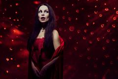Beautiful vampire woman in red dress Stock Photos